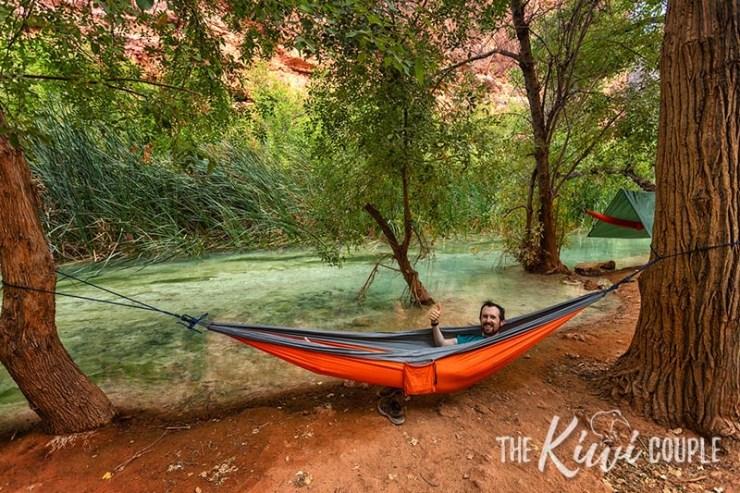 Jeremy in an orange hammock hanging by the clear Havasupai waters