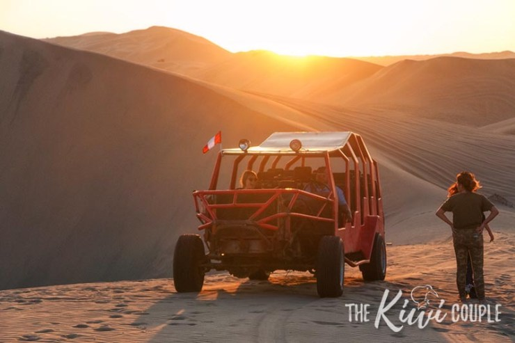 A sand buggy on the dunes of Huacachina at sunset, with a golden glow
