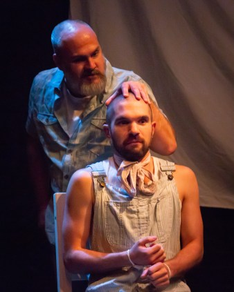 Raff (Craig Houk) assesses the head of Rolly (Grant Collins). Photo by Ryan Maxwell Photography.