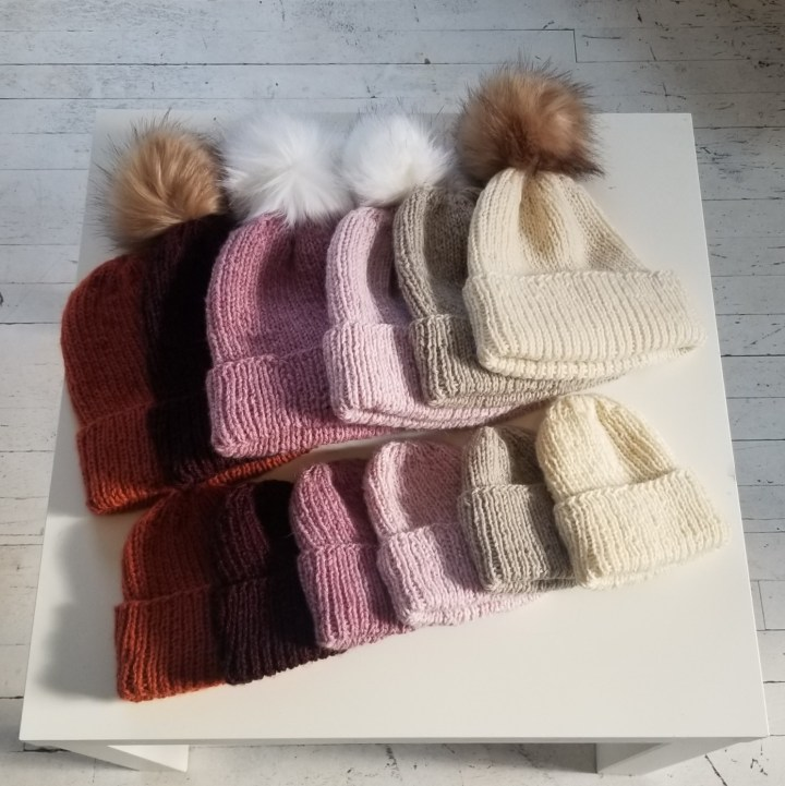 Image of the Anchored hat knit in a variety of colors, fanned out on a table.