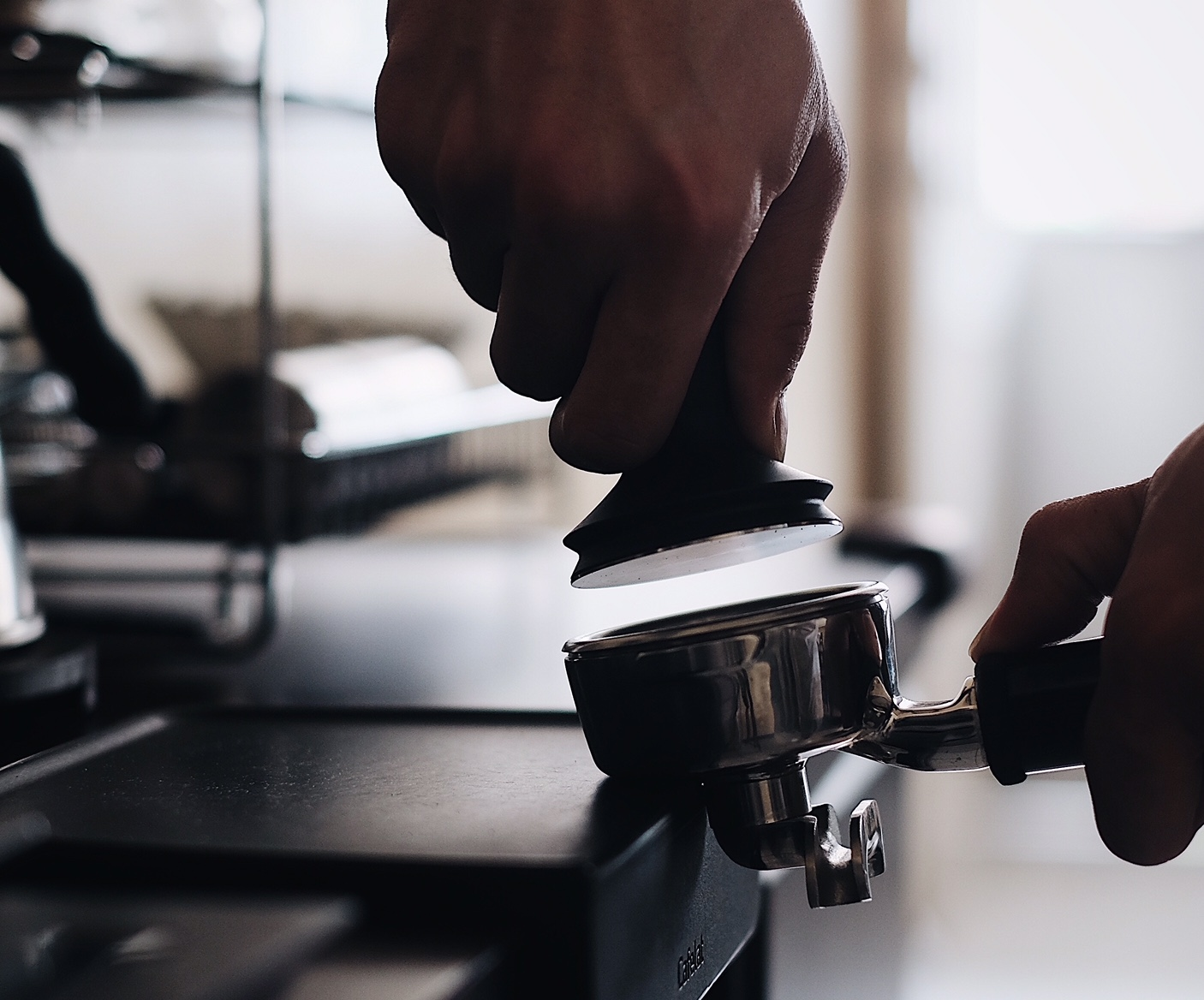 A hand holds a tamper just after using it to compact espresso grounds before pulling a shot.