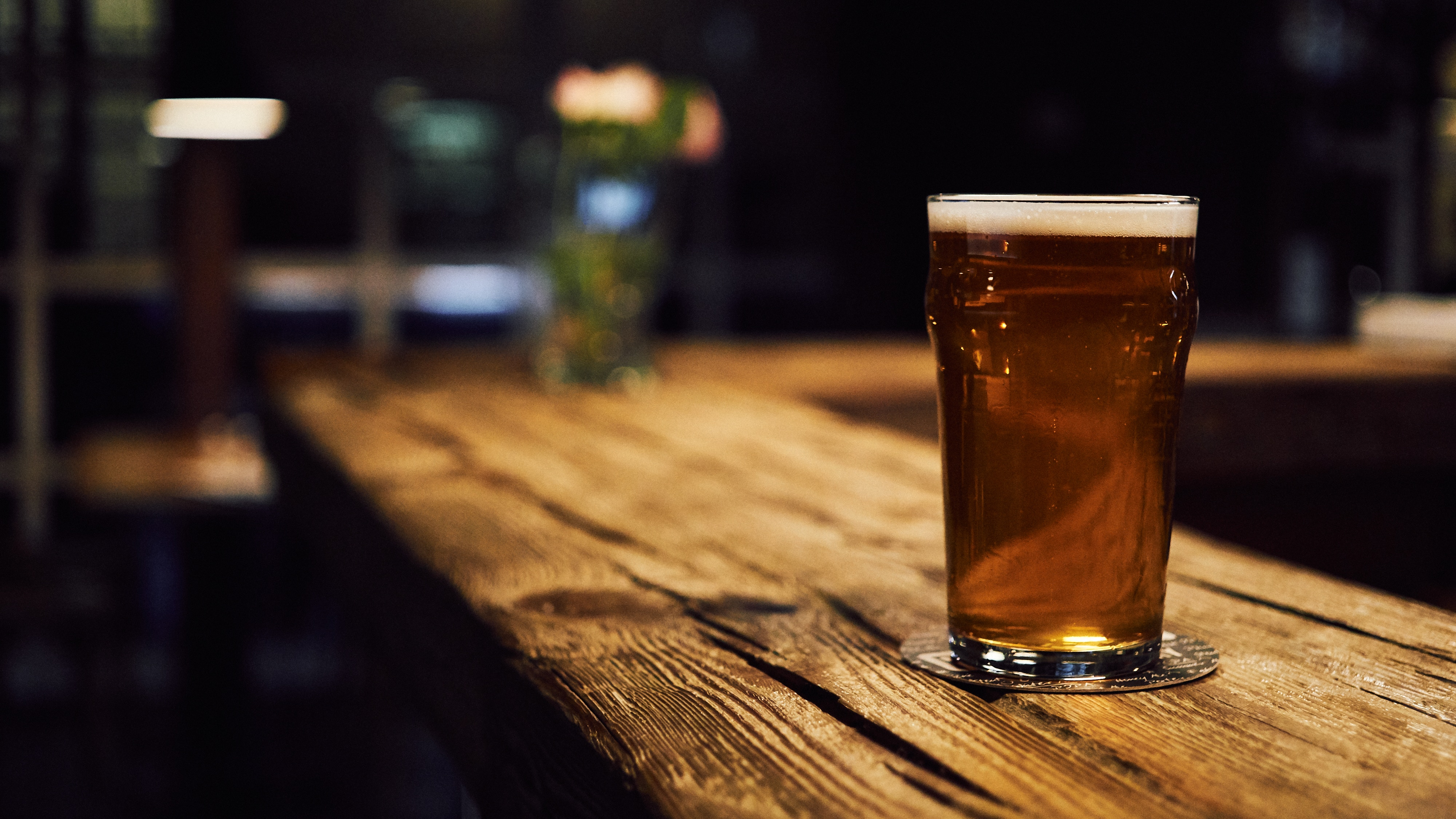 A tall glass of dark beer sits alone on a long wooden counter in a well-lit bar.