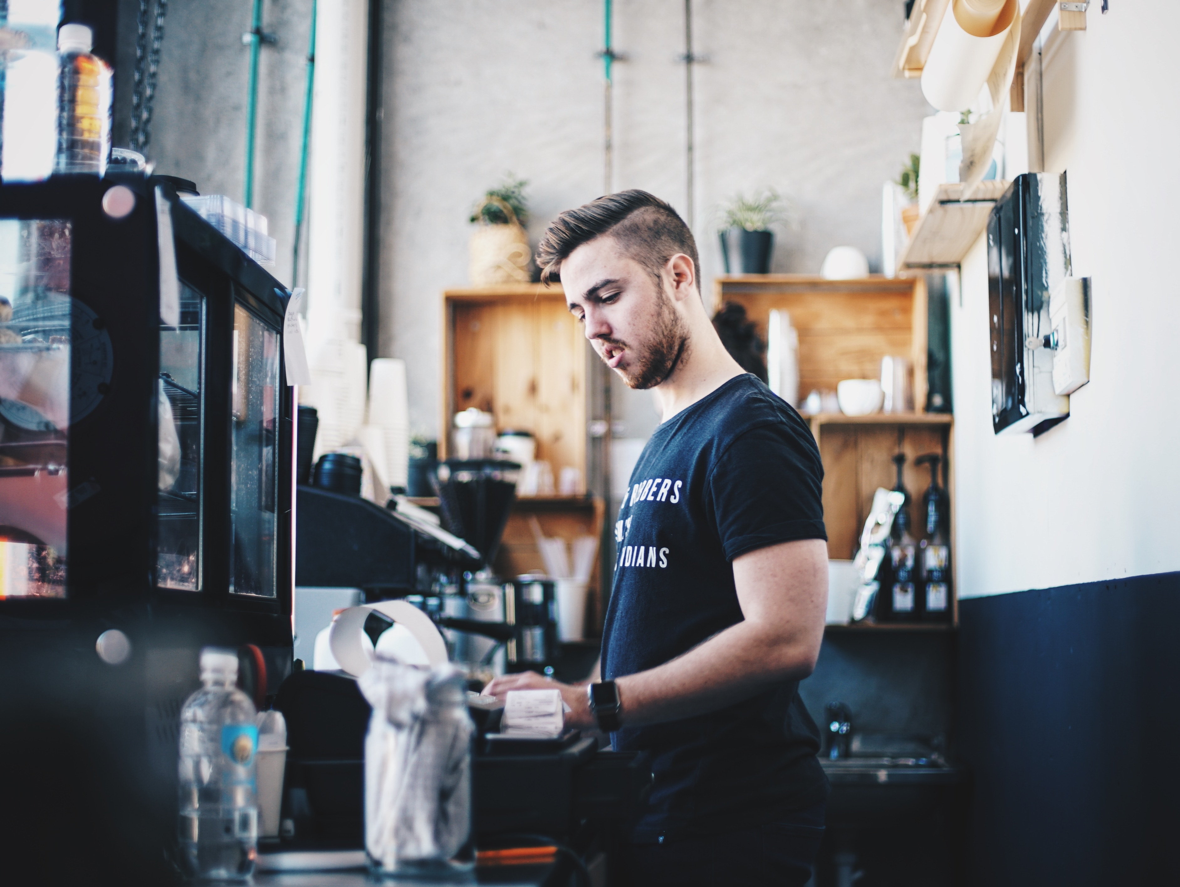 A barista in a black shirt and plants stands at the bar in a cafe.