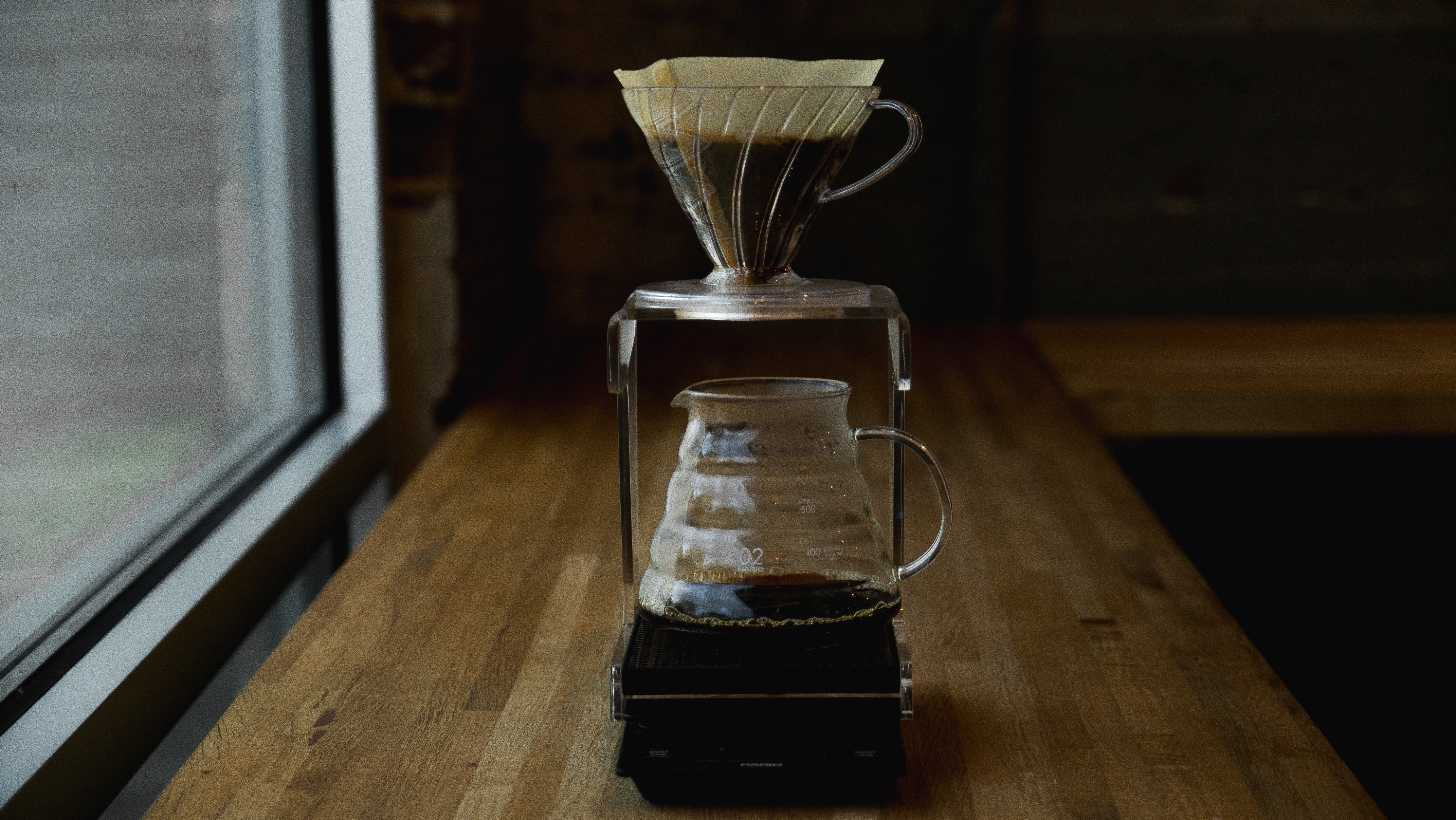 A pourover sits atop a glass decanter full of hot coffee on a wooden table in front of a window.
