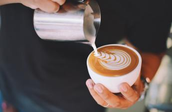 A hand pours latte art from a silver pitcher into a white cappuccino cup.