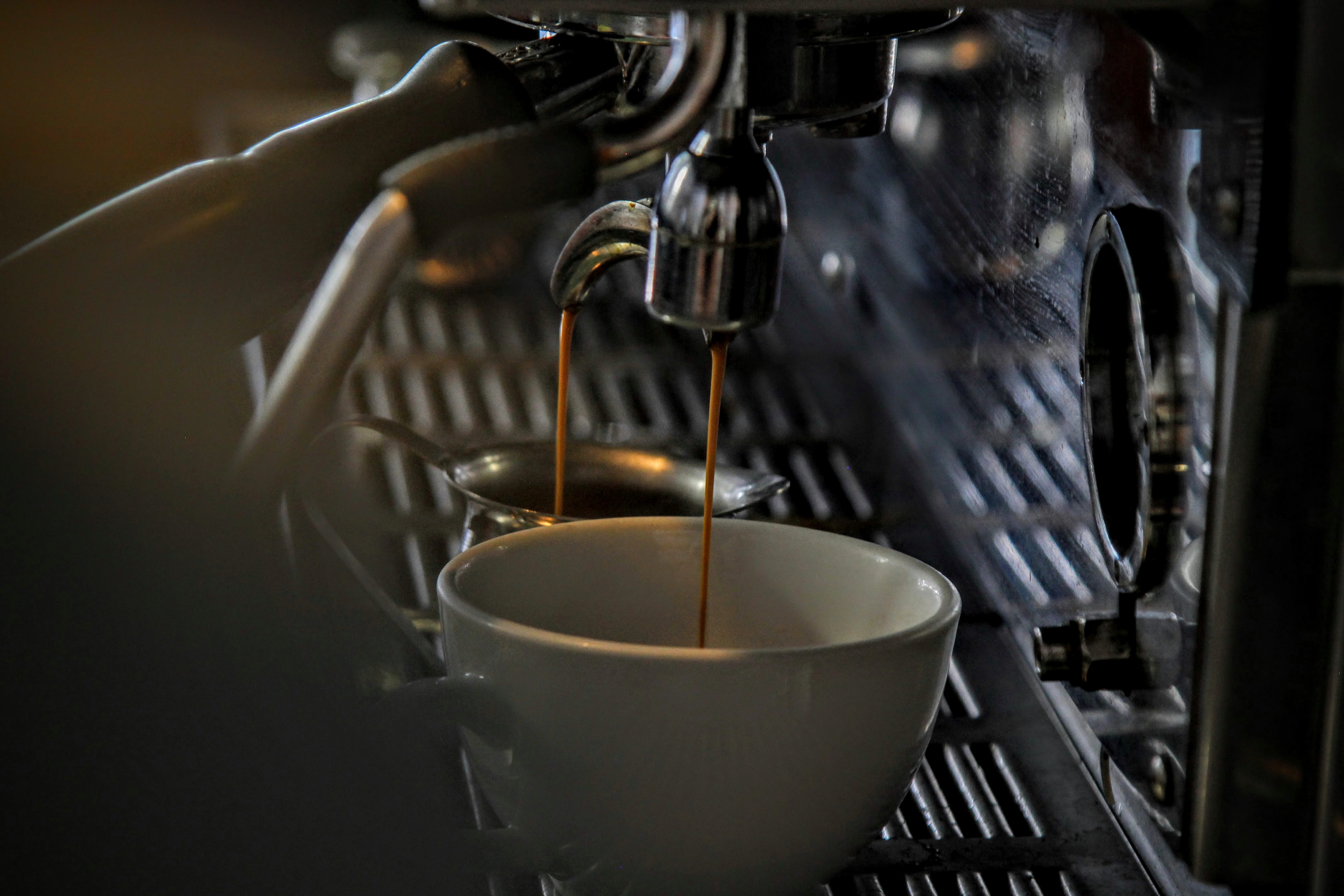 An espresso shot pulls into a white cup in a dim atmosphere.