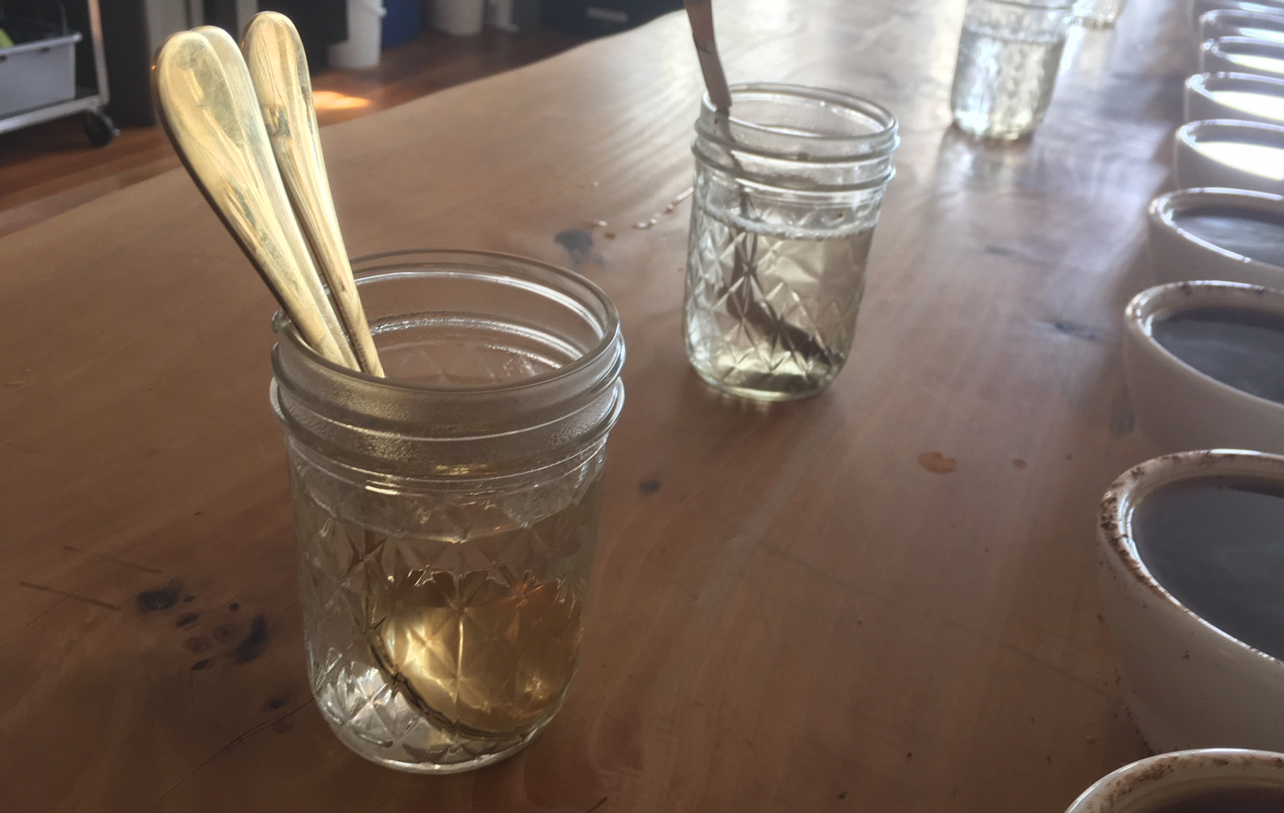 Golden cupping spoons in a rinse cup on a wooden table.