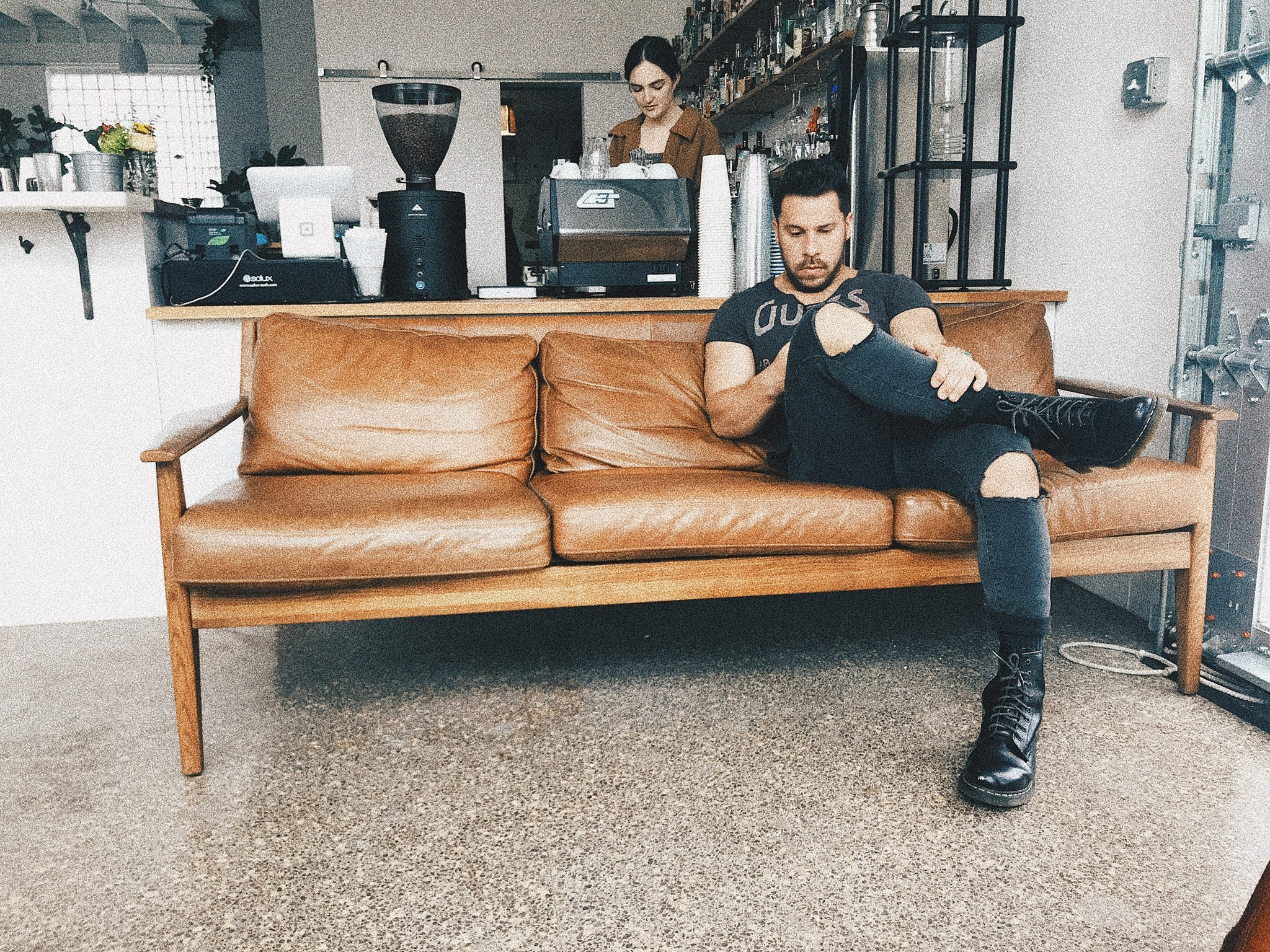 A cafe with a couch and a man on it.