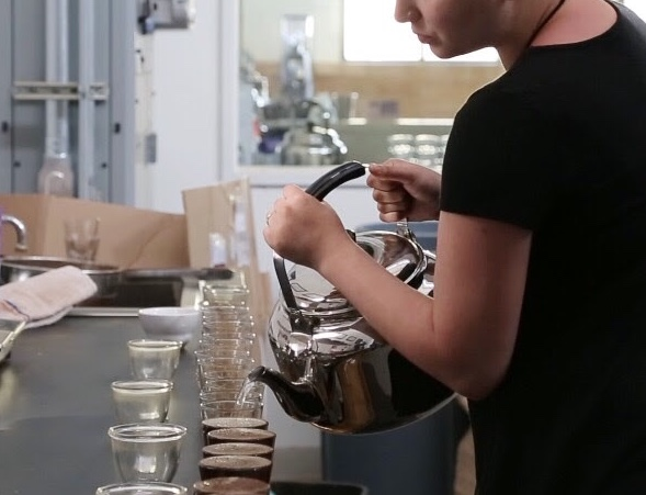 A person in a black shirt pours the water for a cupping.