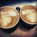 Two cappuccinos with latte art dicks.