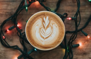 A cappuccino with Christmas lights around it.