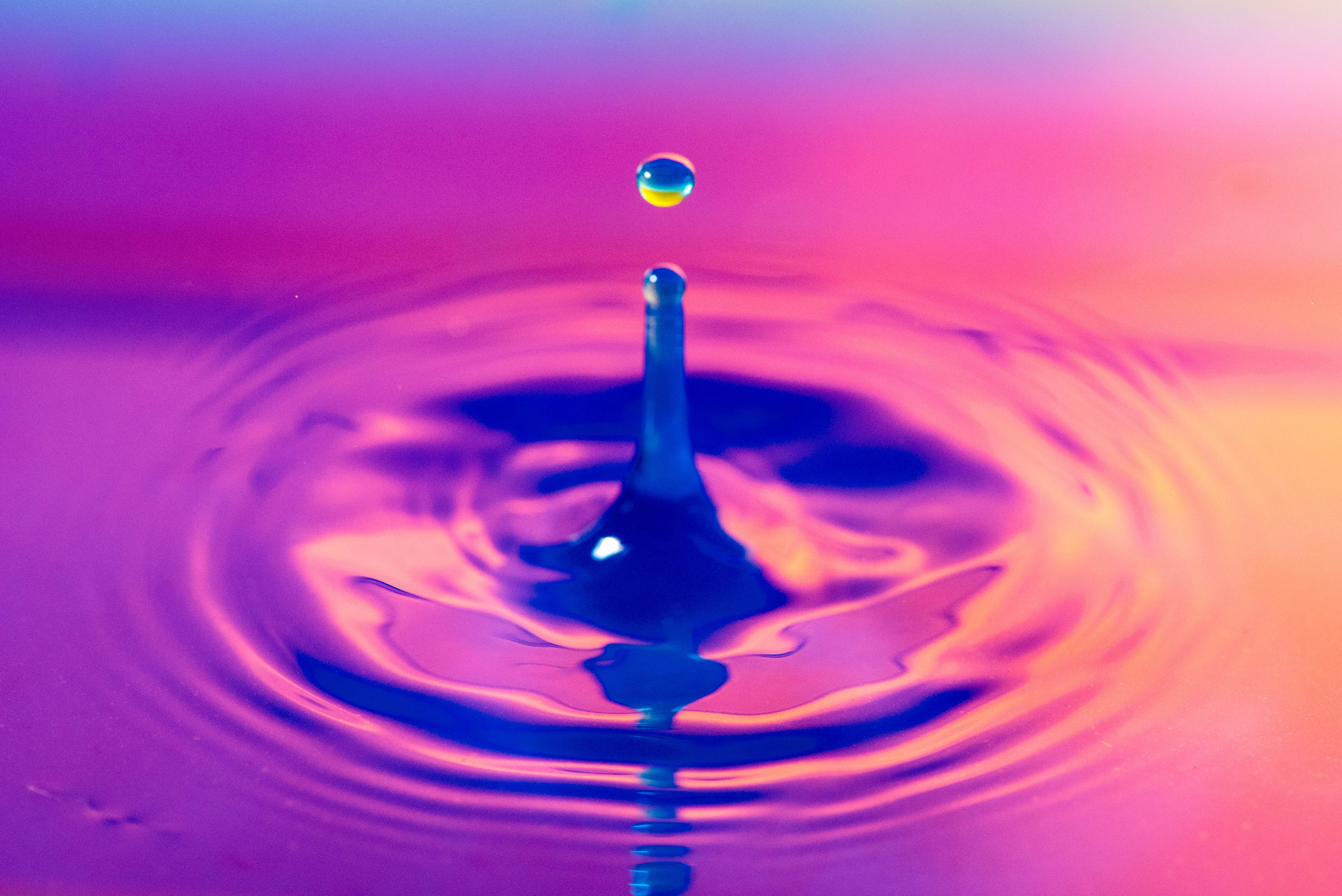 A droplet of water falling into a pool, all tinted purple and orange.