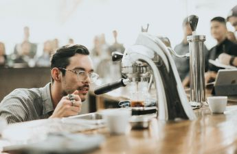 A barista looks in wonder at the shot he's pulling.