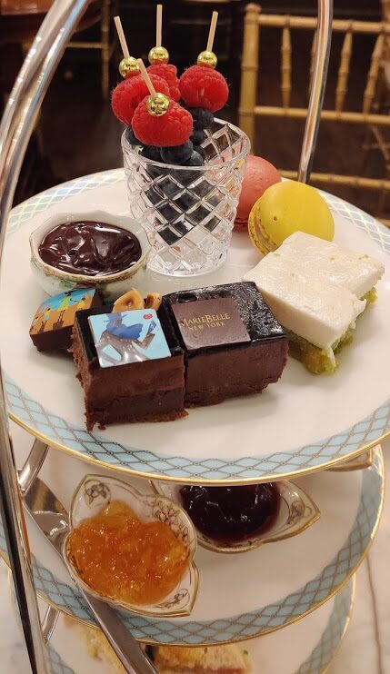 A tiered serving tray with fruit, chocolates, scones, and sandwiches