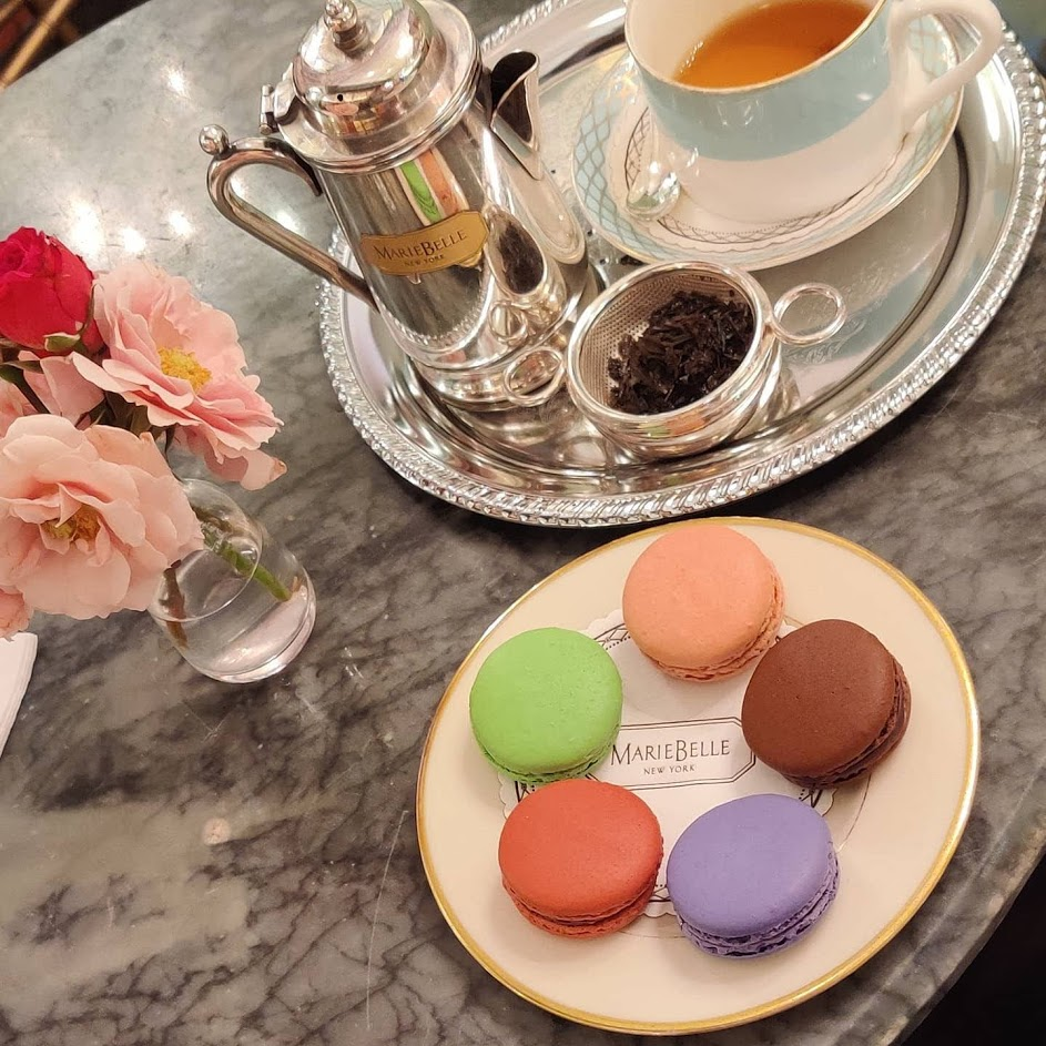 Macarons, tea on a silver tray, and flowers