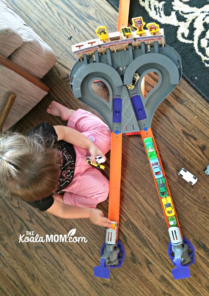 Girl playing with the HotWheels car launcher