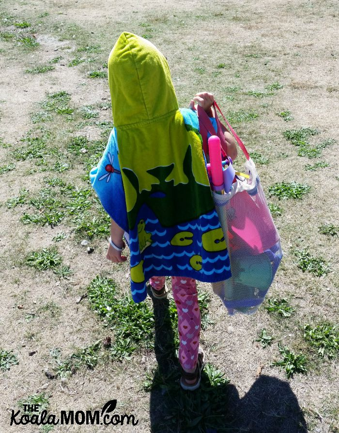 Sunshine leaving the beach, with her beach towel and toys