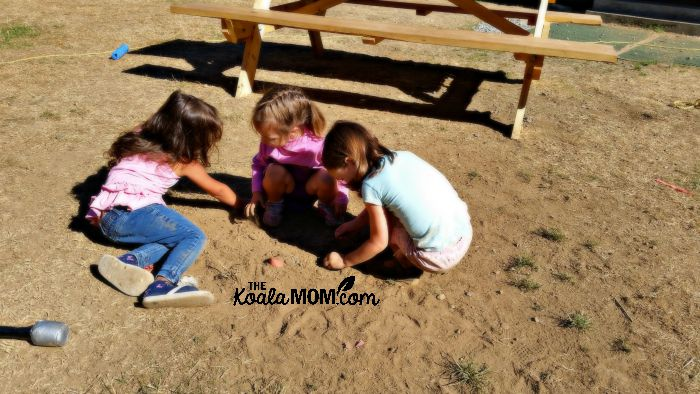 Jade and Lily and a friend playing in the dirt at camp