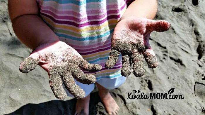 Jade's sandy hands at Mystic Beach
