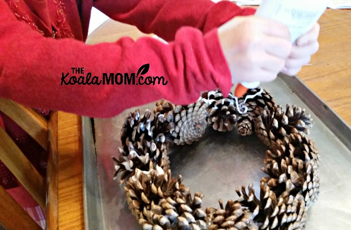 Sunshine putting glue on a pine cone wreath to decorate it