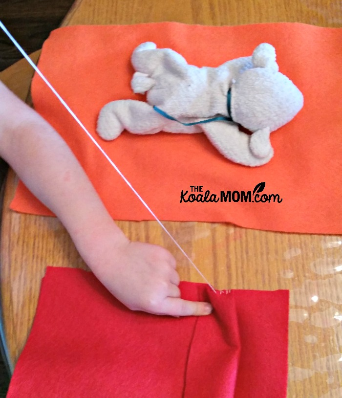 Lily sewing a sleeping bag for her stuffed lamb