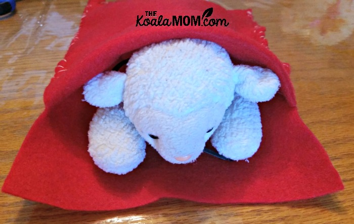 Beany Baby lamb tucked inside her felt sleeping bag
