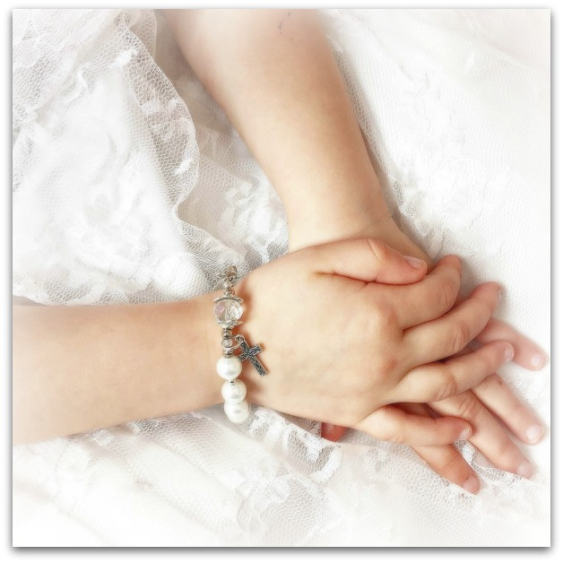Girls' hands clasped with a rosary bracelet on her wrist