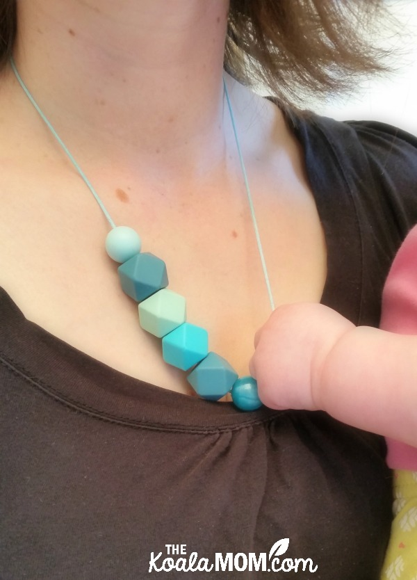 Baby holding a mom's teething necklace (one of my favourite teething solutions)