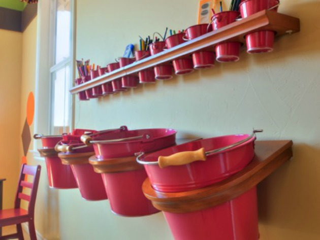 Pails hanging on wall to organize children's toys and art supplies