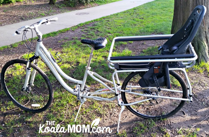 A cargo bike with baby seat on the back