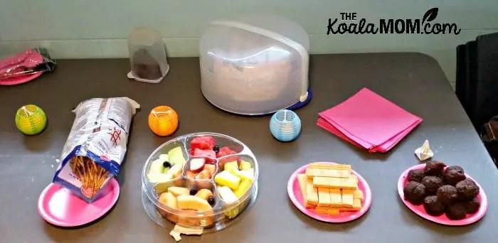 Birthday party snacks - fruit tray, chocolate muffins, prezels, cake.