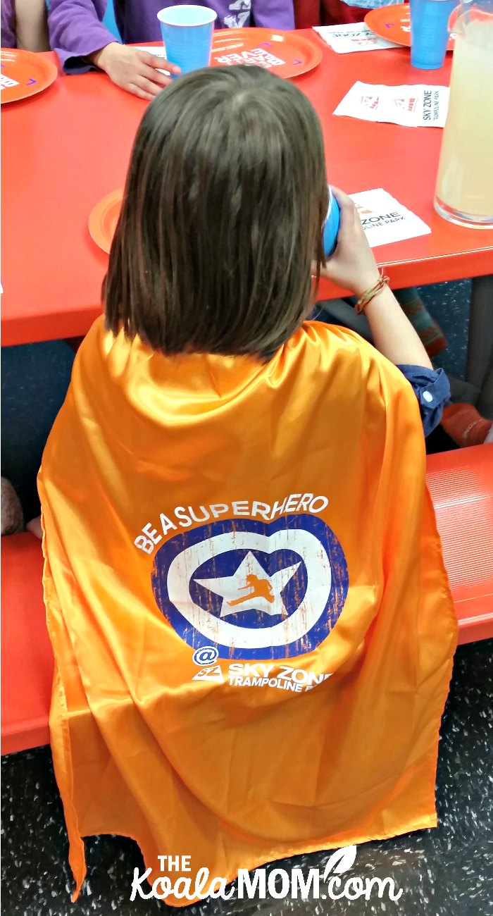 """Jade wearing her """"Be a Superhero"""" orange SkyZone cape at her birthday party."""