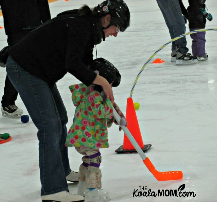 Pregnant mom helping her daughter skate with a hockey stick