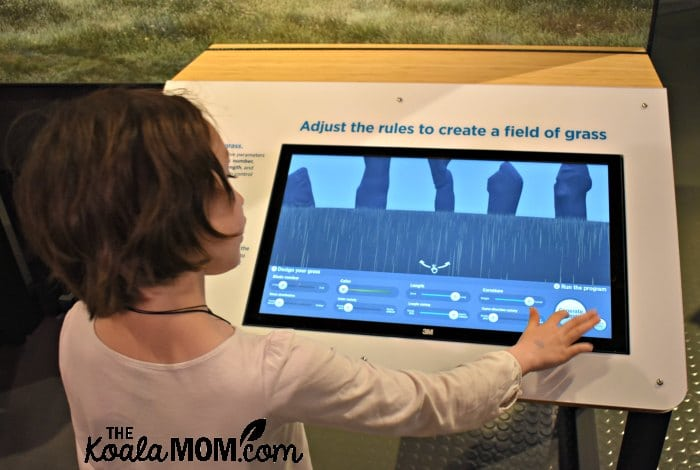 Lily adjusts the computer animation rules to create a field of grass in the Pixar exhibit at the Telus World of Science.