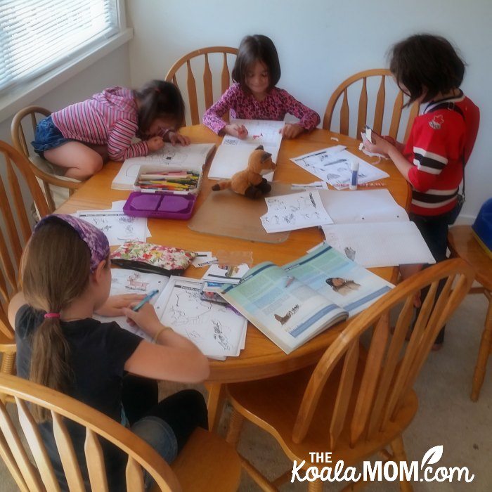 Four sisters doing their homeschool lessons around a dining room table.
