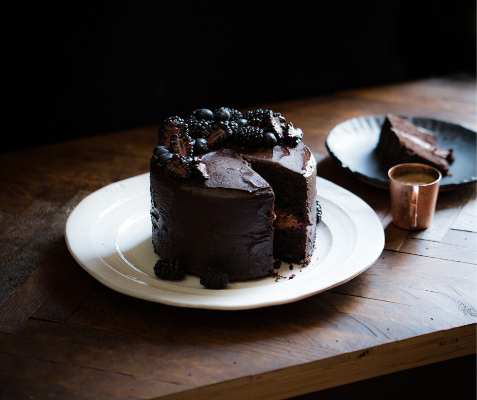 chocolate cake on white plate, sitting on a wooden table