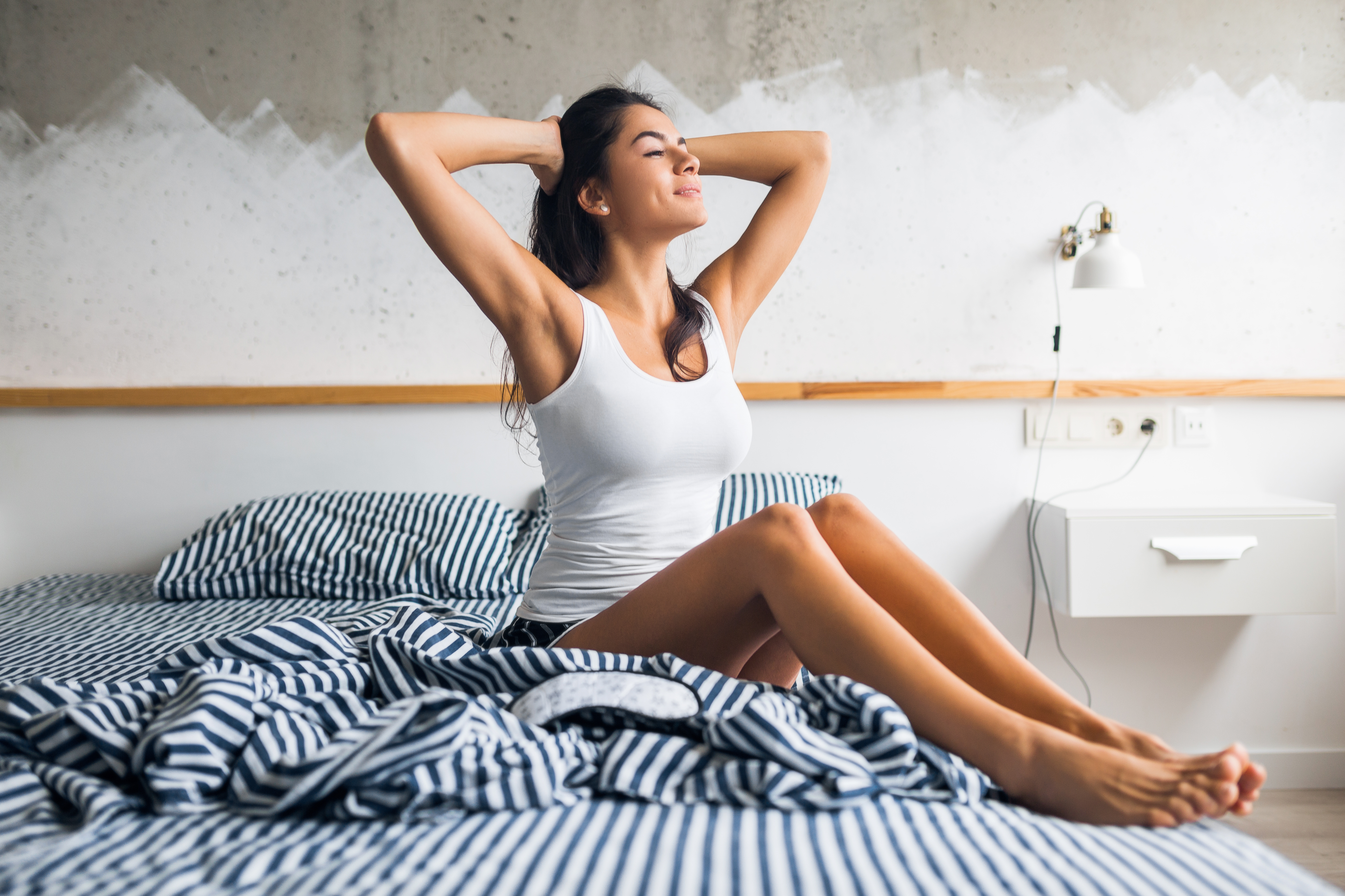 young attractive brunette woman sitting on bed in pajamas and sleeping mask, smiling in bedroom, happy emotion, lazy in morning, waking up, sleepy, sexy, skinny legs