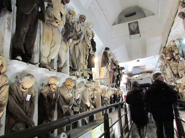 Over 8,000 bodies can be found in the Catacombs of the Capuchin Monks. Pictured is a row of these bodies displayed on the wall behind a barrier.