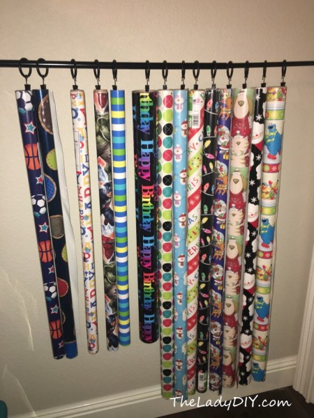 Easy DIY gift wrap storage solution.  Hanging gift wrap, using a curtain rod.