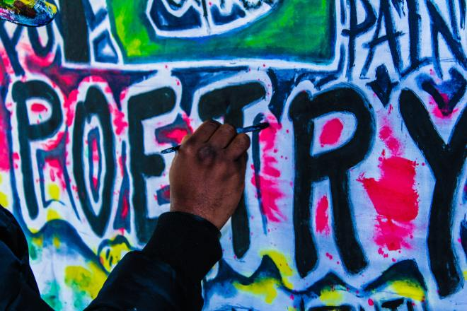 Graffiti wall with the word poetry being painted.