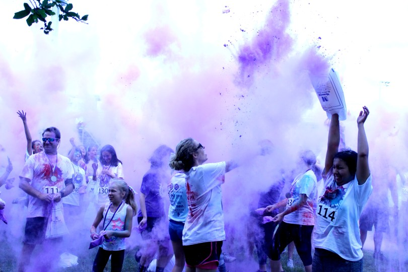 Cooper City participants throw purple pigment into the air after the Color Run.