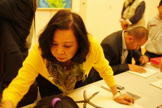 """Artist Hai-Ping Lee doing an art demo at """"So This is Canada!"""" 
