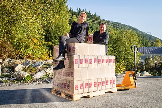 Natasha and Norm Strim sitting on some pallets of their balsamic reductions | Photo courtesy of Natasha Strim