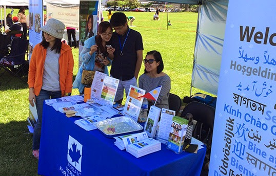 Kim Tan (in sunglasses) mans a MOSAIC booth at a community event   Photo by Erica Huang