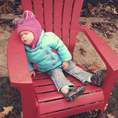 sleeping bundled up outside in chair