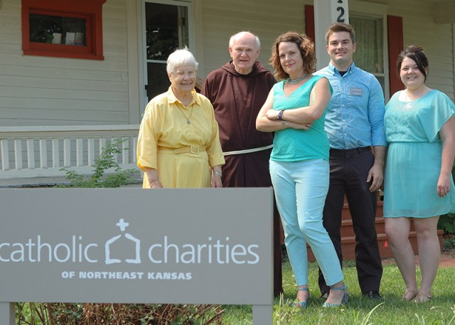 Built in 1880, this Lawrence home was renovated by St. John the Evangelist parishioners and donated as an emergency assistance center to Catholic Charities of Northeast Kansas. Standing in front (from left) are Ursuline Sister Marcella Schrant, Father Mike Scully, OFM Cap., Nickie Daneke, Eric Fitzmorris and Fran Pack.