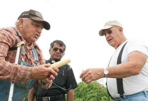 DeMaranville shares some of his corn with pastor Father Mathew Francis and Don Navinsky, parish council vice president.