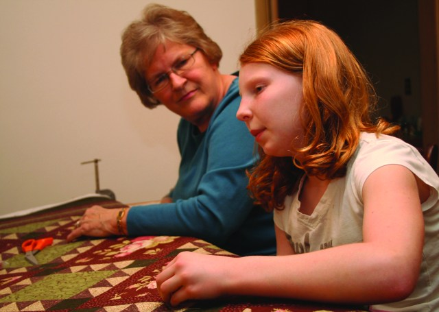 Penny Zweimiller, a member of St. Joseph Parish, Flush, teaches her 11-year-old granddaughter Jana Kellogg how to quilt. For nearly 100 years, quilters from St. Joseph have been building quilts to be raffled at the parish's annual picnic.