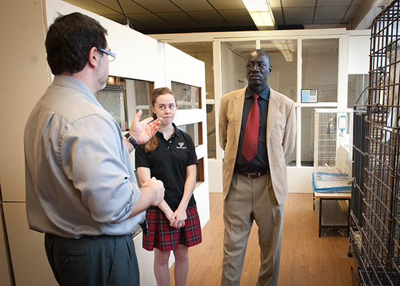 LEAVEN PHOTO BY LORI WOOD HABIGER The Hon. Ronald Reagan Okumu, right, a parliamentarian from Uganda, takes a tour of Bishop Ward High School on Feb. 12. Science teacher Ignacio Martinez-Alonso talks to Okumu about the school, while student guide senior Theresa Collins looks on. Okumu hopes to foster a relationship between Ward and a school in Uganda.