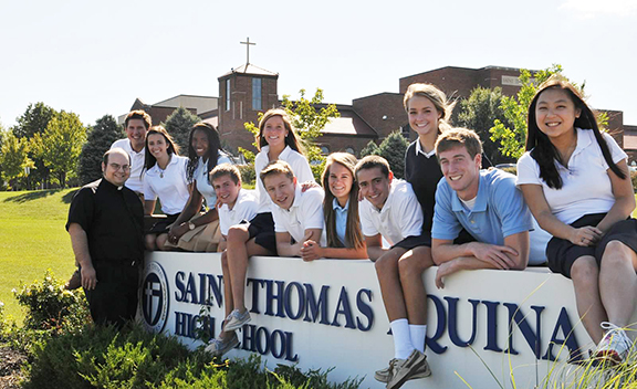 From left to right, Aquinas students Ryan Pottier, Mary Fortino, Lauren Holley, Tyler Heying, Clare Eagan, Jimmy Clark, Katie Ahern, Wade Parks, Margaret Skorija, John Ekedahl, and Theresa Wynne pose with Father Andrew Strobl, chaplain of Aquinas, in front of the school last year. Aquinas was named as a 2012 Blue Ribbon School. Photo by Michelle Gress